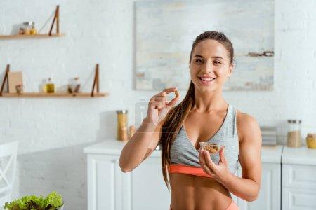 Photo pour Femme sportive heureuse retenant l'amande et souriant à la maison - image libre de droit
