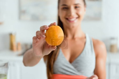 selective focus of happy young woman holding tasty orange