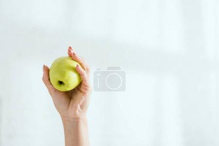 Photo pour Vue recadrée de femme retenant la pomme organique verte - image libre de droit
