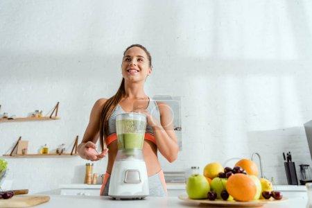Photo pour Vue d'angle bas de la femme gaie près du mélangeur avec le smoothie - image libre de droit