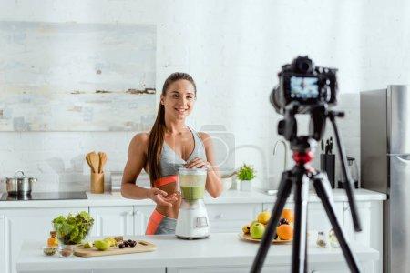 Photo pour Foyer sélectif de femme gaie près du mélangeur avec smoothie - image libre de droit
