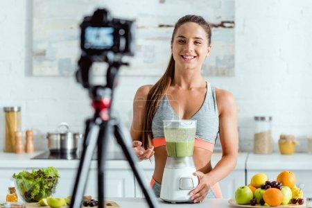 Photo pour Foyer sélectif de gaie sportive gesticulant près de smoothie dans le mélangeur - image libre de droit