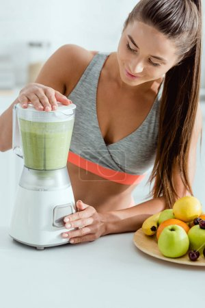 Photo for Selective focus of attractive sportswoman preparing smoothie in blender - Royalty Free Image