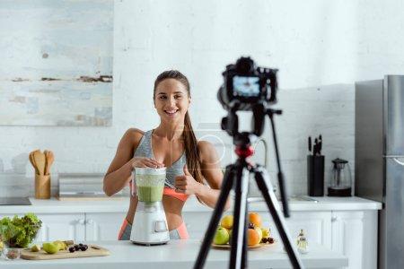 Photo pour Foyer sélectif de fille gaie montrant pouce vers le haut près de smoothie dans le mélangeur et appareil photo numérique sur trépied - image libre de droit