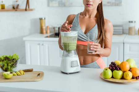 Photo for Cropped view of sportswoman standing near blender with smoothie and fruits - Royalty Free Image