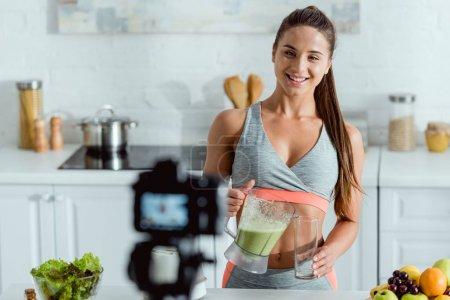 Photo pour Foyer sélectif de fille heureuse verser smoothie en verre et en regardant appareil photo numérique - image libre de droit