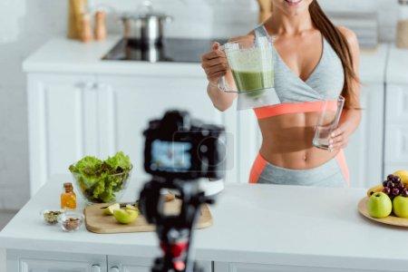 Photo pour Foyer sélectif de fille heureuse tenant smoothie en verre près de l'appareil photo numérique - image libre de droit