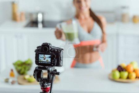 Photo pour Mise au point sélective de l'appareil photo numérique avec fille heureuse tenant smoothie en verre à l'écran - image libre de droit