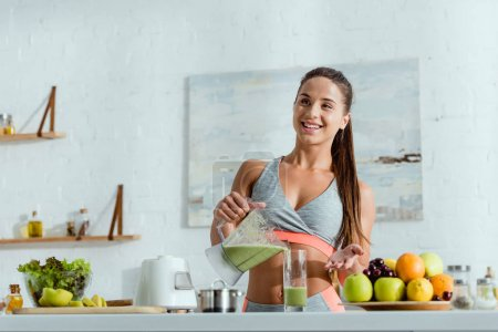 selective focus of cheerful girl holding glass while pouring smoothie from blender near fruits