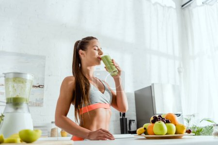 Photo for Low angle view of girl drinking green fresh smoothie - Royalty Free Image