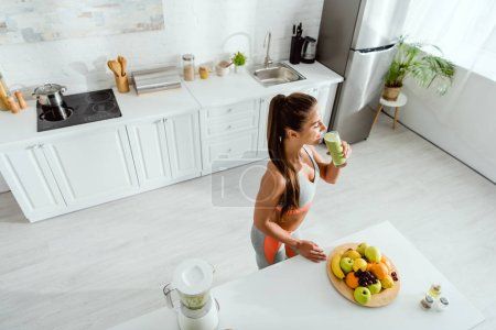 Photo for Overhead view of woman drinking smoothie near fruits in kitchen - Royalty Free Image