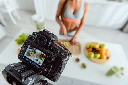 Photo for Selective focus of digital camera with girl cutting apple on screen - Royalty Free Image