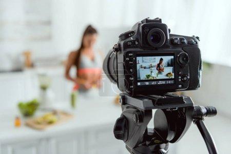 Photo pour Foyer sélectif de l'appareil-photo numérique avec la fille près du verre avec la boisson et les fruits sur l'écran - image libre de droit