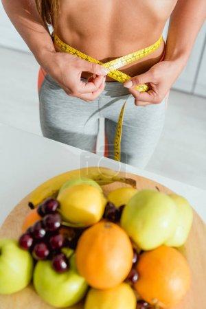 Photo pour Vue recadrée de la femme retenant le ruban de mesure tout en mesurant la taille près des fruits - image libre de droit
