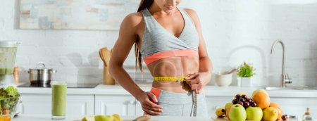 Photo for Panoramic shot of sportive woman measuring waist near fruits - Royalty Free Image