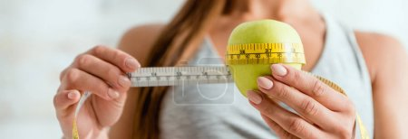 Photo pour Plan panoramique de la jeune femme mesurant la pomme verte - image libre de droit