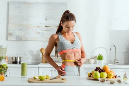 Photo for Young woman measuring waist near fruits and drink - Royalty Free Image