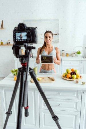 Photo pour Foyer sélectif de blogueur vidéo heureux tenant tablette numérique avec écran blanc - image libre de droit