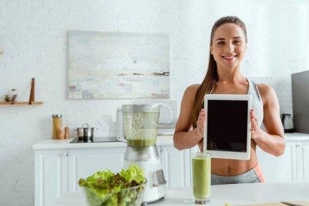 Photo pour Femme heureuse tenant tablette numérique avec écran vide près du mélangeur et du verre avec smoothie - image libre de droit