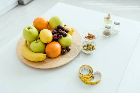 Photo for Selective focus of tasty and ripe fruits on plate near measuring tape on table - Royalty Free Image