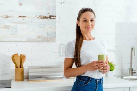 Photo pour Fille heureuse souriant tout en retenant le verre avec le smoothie vert - image libre de droit