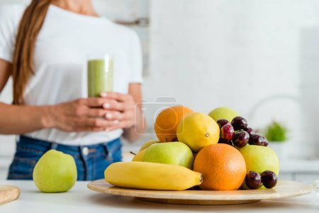 Photo pour Foyer sélectif de fruits délicieux mûrs près fille tenant verre avec smoothie vert - image libre de droit