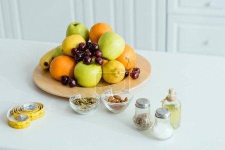 Foto de Frutas sabrosas y maduras en el plato cerca de cinta de medición en la mesa - Imagen libre de derechos