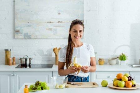 Photo pour Heureux fille coupe banane sur peeling board près de savoureux fruits - image libre de droit