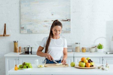 happy girl cutting banana on cutting board near tasty fruits