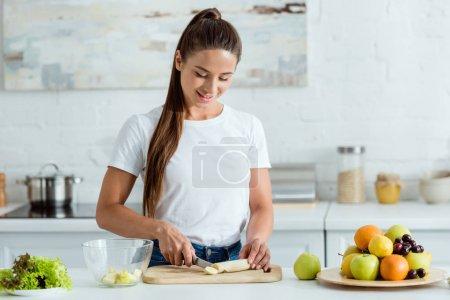 Photo pour Gai fille coupe savoureuse banane sur planche à découper près de fruits - image libre de droit