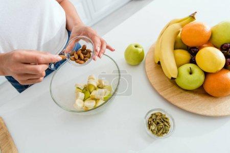 Photo pour Vue recadrée de femme ajoutant des amandes dans le bol près des fruits savoureux - image libre de droit