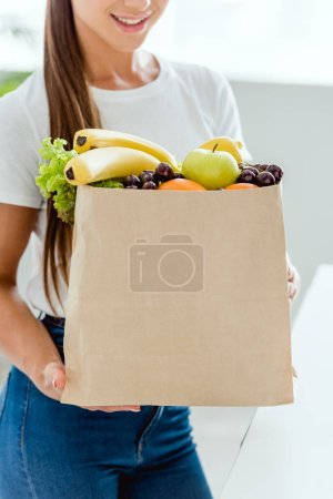 cropped view of happy woman holding paper bag with organic fruits