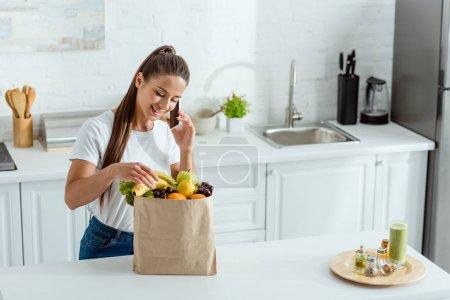 Photo pour Heureuse jeune femme parlant sur smartphone près du sac en papier avec des fruits - image libre de droit