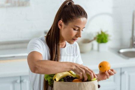 Photo pour Jeune femme regardant sac en papier et toucher des fruits biologiques - image libre de droit