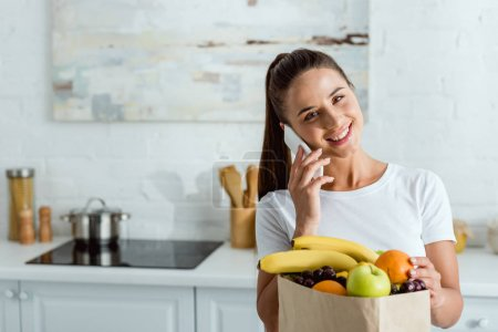 happy woman talking on smartphone near paper bag with delicious fruits