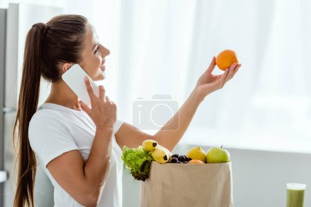 Photo for Happy woman talking on smartphone near paper bag with groceries - Royalty Free Image