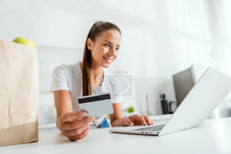 selective focus of happy girl holding credit card and using laptop