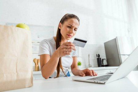 Photo pour Foyer sélectif de la fille regardant la carte de crédit et utilisant l'ordinateur portatif - image libre de droit