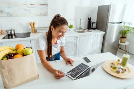 Photo pour Femme gaie en utilisant un ordinateur portable près du smartphone avec écran vierge - image libre de droit