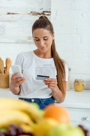 Photo pour Foyer sélectif de fille gaie en utilisant smartphone et tenant la carte de crédit - image libre de droit