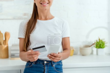 Photo for Cropped view of happy woman holding smartphone and credit card - Royalty Free Image