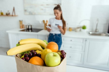 Photo pour Foyer sélectif de la femme heureuse en utilisant un smartphone et tenant la carte de crédit - image libre de droit