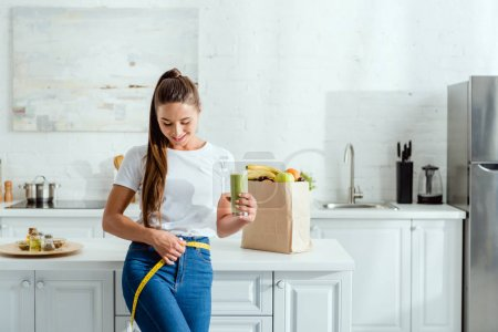 Photo for Happy young woman measuring waist and holding glass with smoothie near groceries - Royalty Free Image