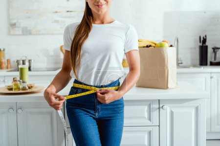 Photo for Cropped view of happy young woman measuring waist near groceries - Royalty Free Image
