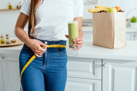 Photo for Cropped view of young woman measuring waist near groceries - Royalty Free Image