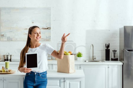 Photo pour Joyeuse fille tenant tablette numérique avec écran blanc et pointant du doigt près des épiceries - image libre de droit