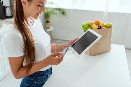 Szczęśliwa młoda kobieta trzyma tablet cyfrowy z pustym ekranem i kartą kredytową