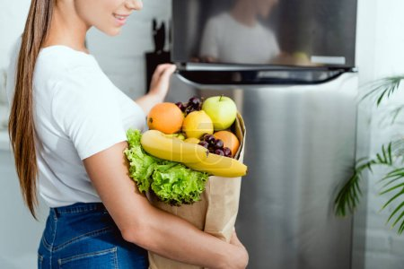 Photo for Cropped view of happy girl opening fridge and holding groceries - Royalty Free Image
