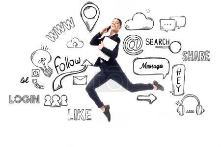 Photo pour Femme d'affaires souriante parlant sur smartphone et tenant un ordinateur portable tout en lévitant près de l'illustration avec des icônes multimédias et des logos isolés sur blanc - image libre de droit