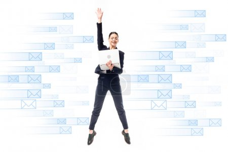 Photo for Smiling businesswoman using laptop while jumping on background with e-mail icons isolated on white - Royalty Free Image